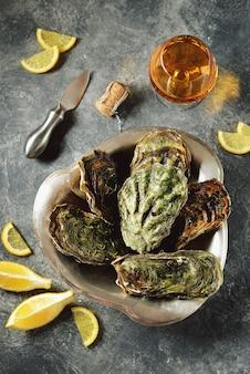 Ostriche chiuse con fette di limone su un piatto