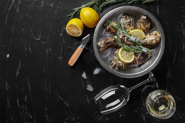 Ostriche chiuse fresche, ghiaccio, limone su una piastra di metallo rotonda