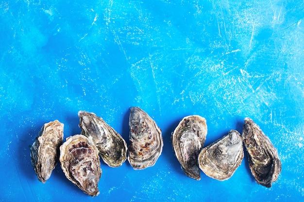 Ostriche chiuse su sfondo blu con spazio di copia. frutti di mare sani