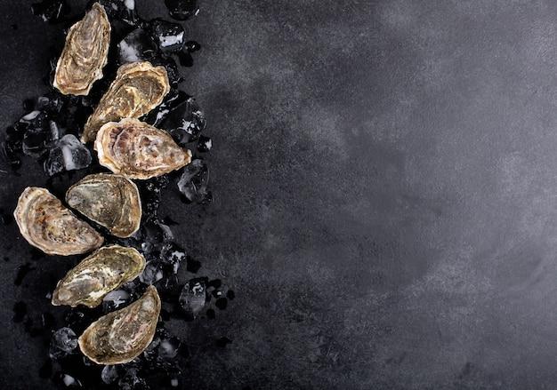 Ostriche e ghiaccio chiusi su fondo nero. frutti di mare sani, copia spazio