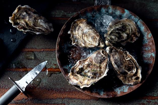 Ostriche fresche aperte su uno sfondo scuro, un coltello e gocce d'acqua. stile rostik.