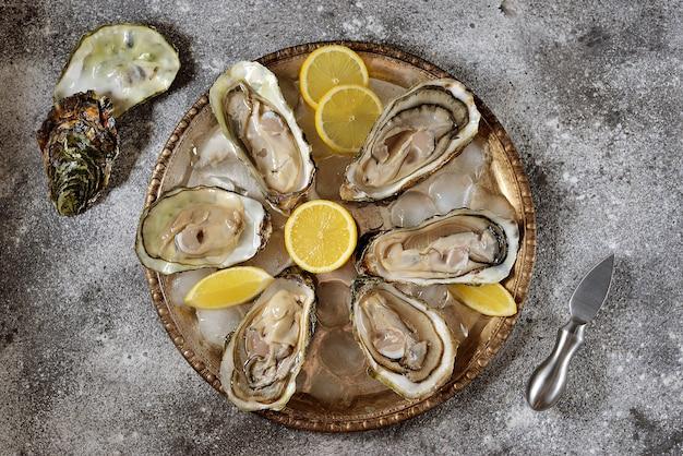 Ostriche fresche con fette di limone su un piatto