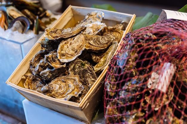 Ostriche fresche con guscio in scatola di legno e rete a buffet.