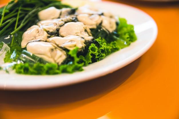 Ostriche fresche in un piatto bianco