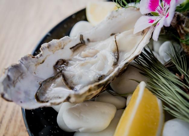 Ostriche fresche su un piatto con ghiaccio e fiori. ristorante