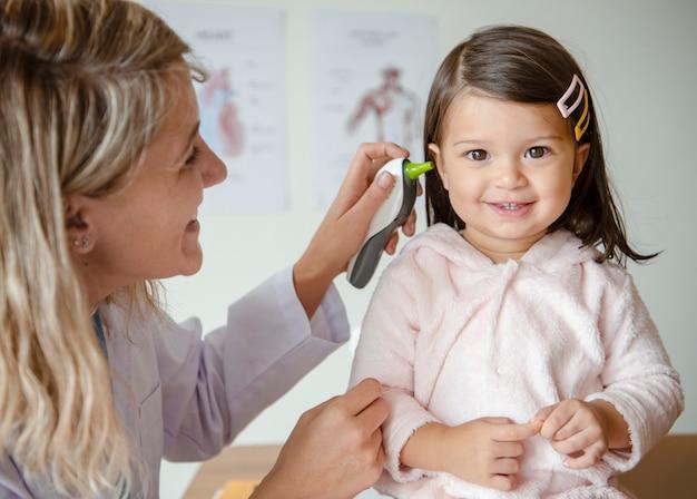 Otorinolaringoiatra che controlla una dolce bambina