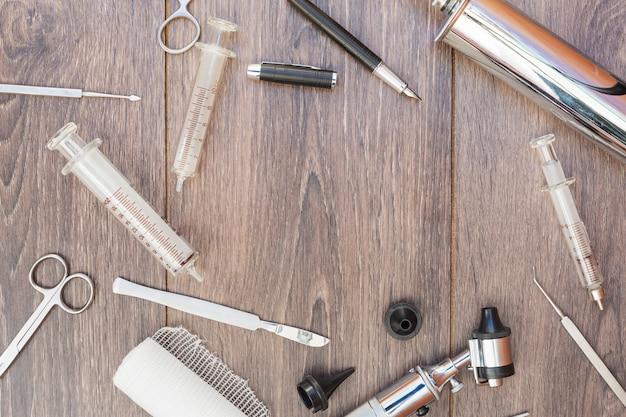 Otoscopio; siringa; strumenti chirurgici; rotolo di garza e penna stilografica nera sulla scrivania in legno