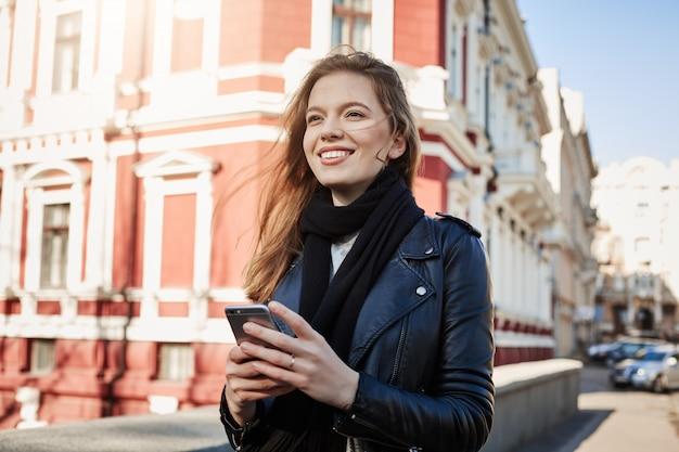Ottima giornata per avventure. ritratto della città della donna europea attraente che cammina in strada, tenendo smartphone