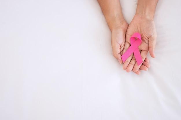 Ottobre mese della consapevolezza del cancro al seno, mano della donna adulta che tiene il nastro rosa per sostenere le persone che vivono e le malattie.