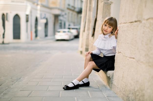 Outdoor fashion street city ritratto di piccola ragazza caucasica. bambina felice che si siede vicino al vecchio muro di costruzione nell'antica città europea con porta blu sullo sfondo