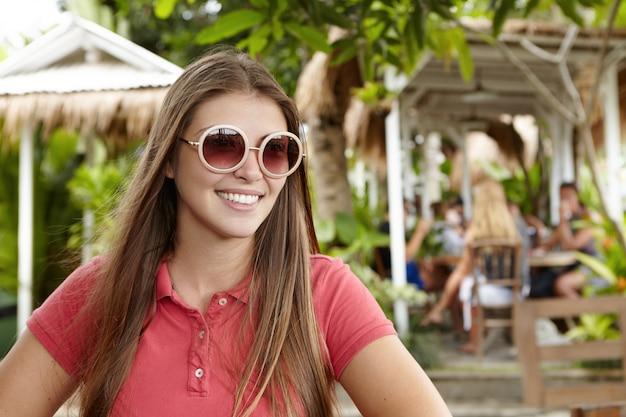 Outdoor ritratto di donna attraente che indossa la maglietta di polo e le tonalità rotonde alla moda che sorridono felicemente, godendo le sue vacanze nel paese tropicale