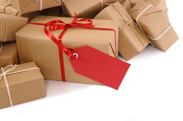 Pacchetti di carta marrone con etichetta regalo rosso