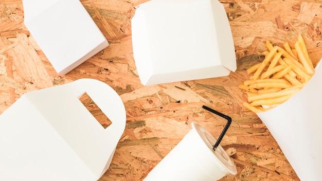 Pacchetto bianco; bevanda usa e getta e patatine fritte su fondo in legno