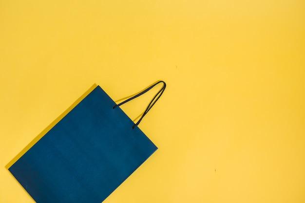 Pacchetto blu su uno sfondo giallo isolato con spazio per il testo