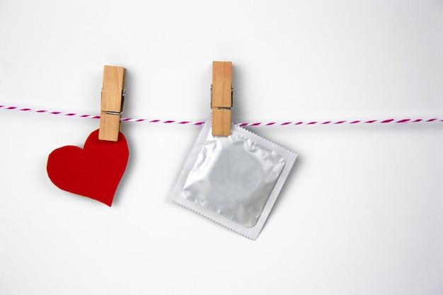 Pacchetto del preservativo sulla molletta per il bucato su un fondo bianco