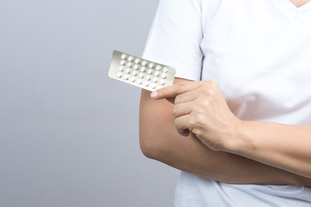 Pacchetto della mano della donna che tiene pacchetto di pillole contraccettive, medicina di controllo delle nascite