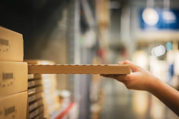 Pacchetto della scatola di cartone con la mano della sfuocatura del prodotto asiatico di raccolto della donna del cliente dallo scaffale in magazzino.