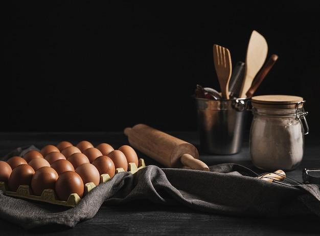 Pacchetto delle uova di vista frontale vicino agli strumenti della cucina