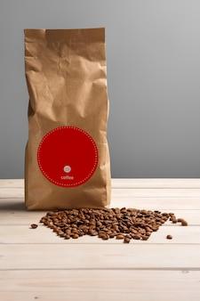 Pacchetto di carta caffè con chicchi di caffè sparsi sul tavolo di legno. copia spazio per il testo.