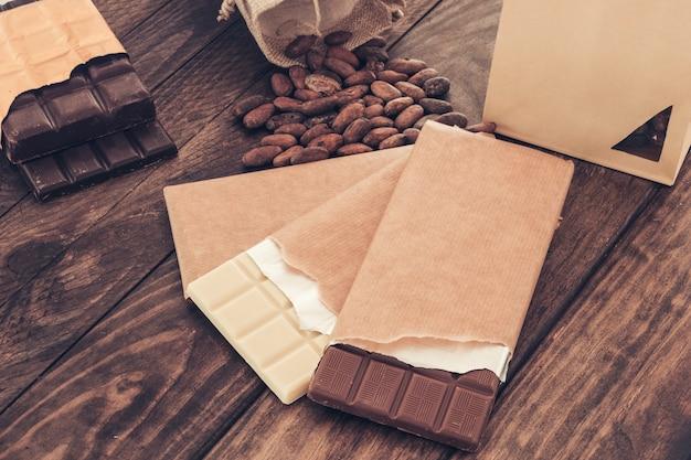 Pacchetto rotto di tavoletta di cioccolato fondente e al latte con fave di cacao sul tavolo
