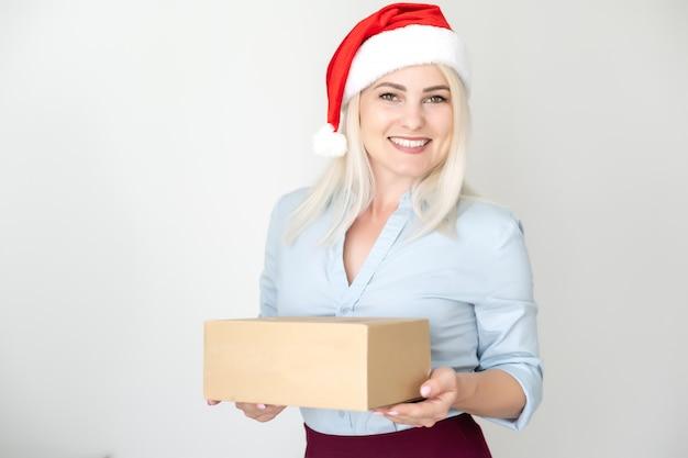 Pacchi di natale di capodanno in scatole, consegna in negozio online, una bella donna con un cappello rosso di babbo natale tiene una pila di scatole.