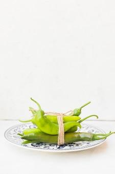 Pacco di peperoncino rosso verde legato con lo spago sul piatto ceramico contro fondo bianco