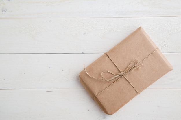 Pacco, regalo imballato in carta ecologica su fondo in legno chiaro. la vista dall'alto