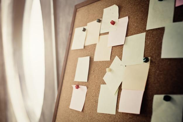 Pad di carta nota su sfondo di ufficio sfocatura woth corkboard