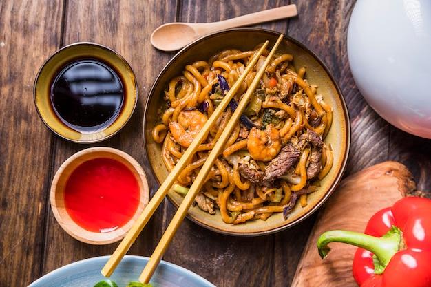 Pad thai con verdure; gamberoni e manzo con salsa di soia sul tavolo di legno