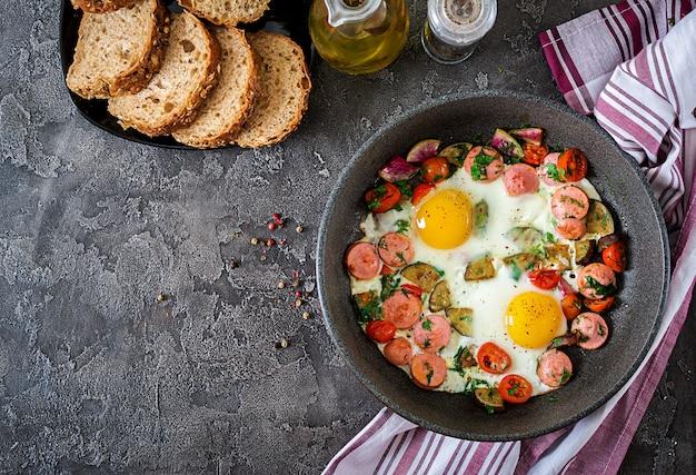 Padella con gustoso uovo cotto, salsicce e verdure sul tavolo grigio. prima colazione. vista dall'alto