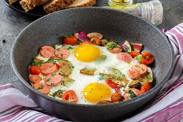 Padella con gustoso uovo cotto, salsicce e verdure sul tavolo grigio. prima colazione.