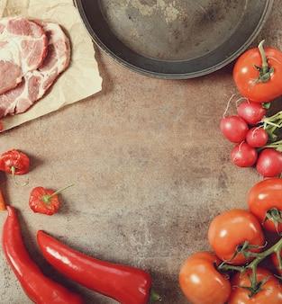 Padella con verdure e carne cruda, vista dall'alto sullo sfondo