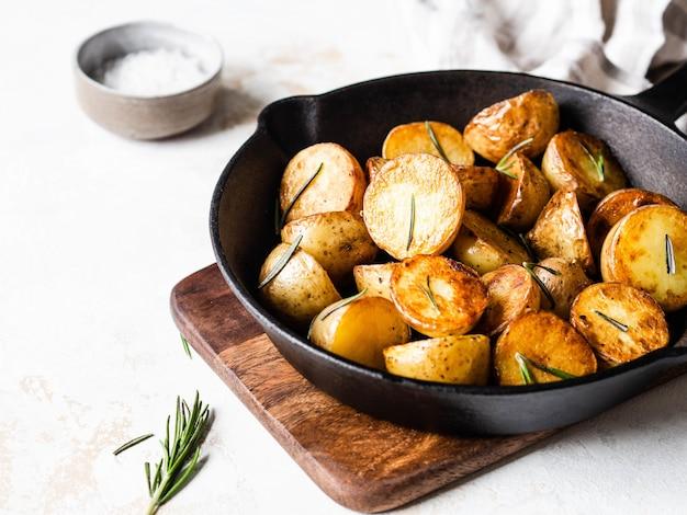 Padella in ghisa nera con spicchi di patate arrosto arrosto con erbe su una superficie leggera
