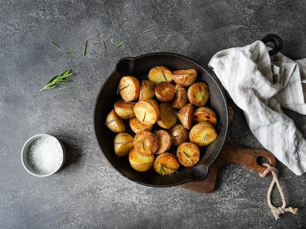 Padella in ghisa nera con spicchi di patate arrosto fritte con erbe su una superficie grigio scuro. vista dall'alto