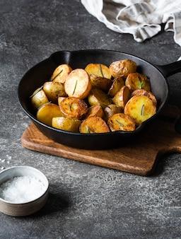 Padella in ghisa nera con spicchi di patate arrosto fritto con erbe su superficie grigio scuro