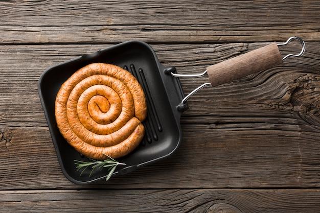 Padella vista dall'alto con deliziosa salsiccia alla griglia