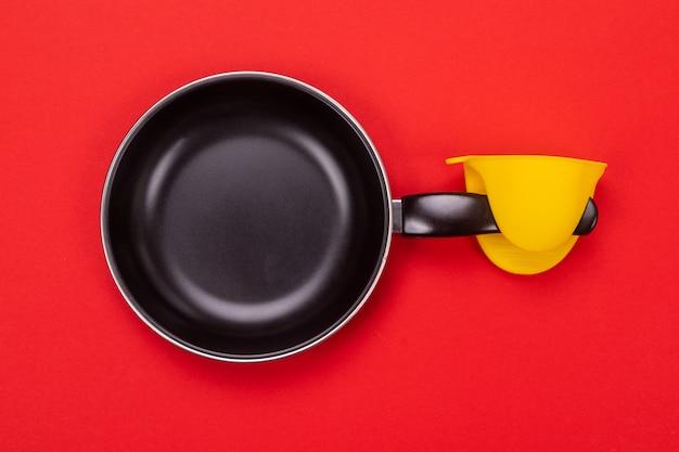Padella vuota della cucina con il guanto da forno su rosso