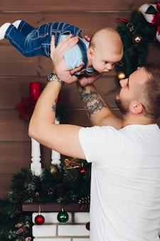 Padre adorabile e felice che tiene il piccolo figlio per mano, sollevandolo