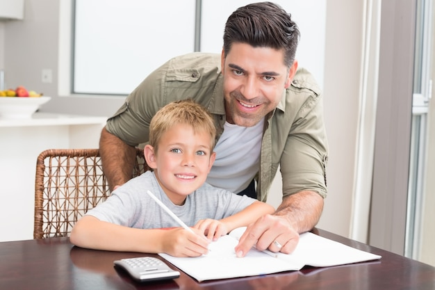 Padre allegro figlio d'aiuto con i compiti di matematica a tavola