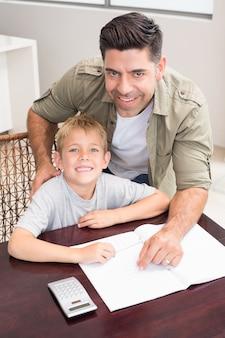 Padre allegro figlio d'aiuto con i suoi compiti di matematica a tavola