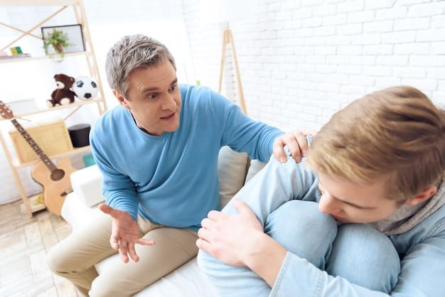 Padre allunga la mano con suo figlio infelice.