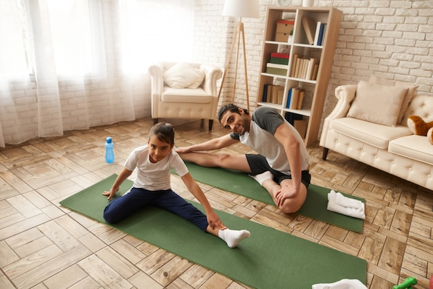 Padre and daughter stretch legs on gym carpet.