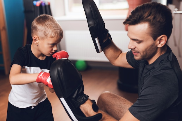 Padre and son boxing exercises training in palestra.