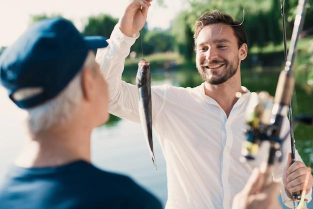 Padre anziano con la pesca del figlio barbuto sul fiume.