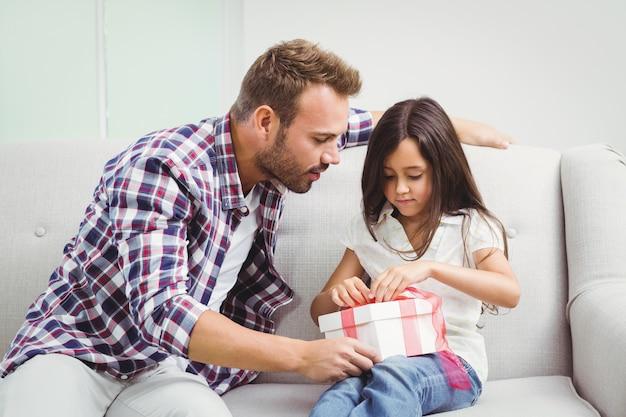 Padre aprendo una confezione regalo con sua figlia