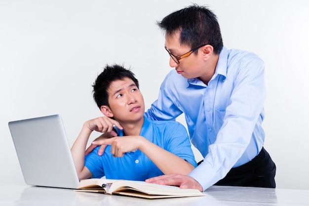 Padre asiatico e figlio che imparano a casa per la scuola