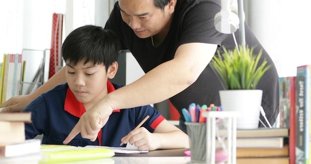 Padre asiatico e figlio facendo i compiti a casa.