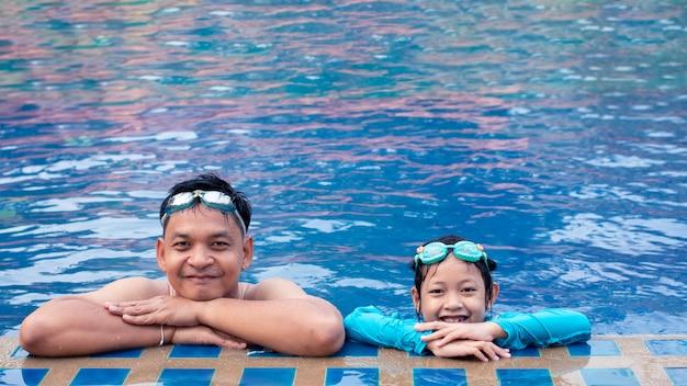 Padre asiatico felice con sua figlia in piscina.