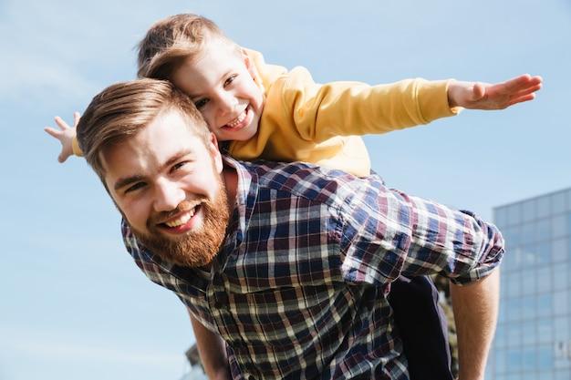 Padre barbuto allegro divertendosi con il suo piccolo figlio