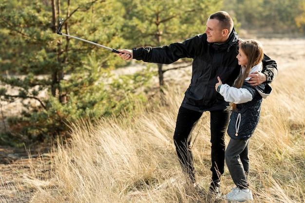 Padre bello che prende un selfie con la figlia